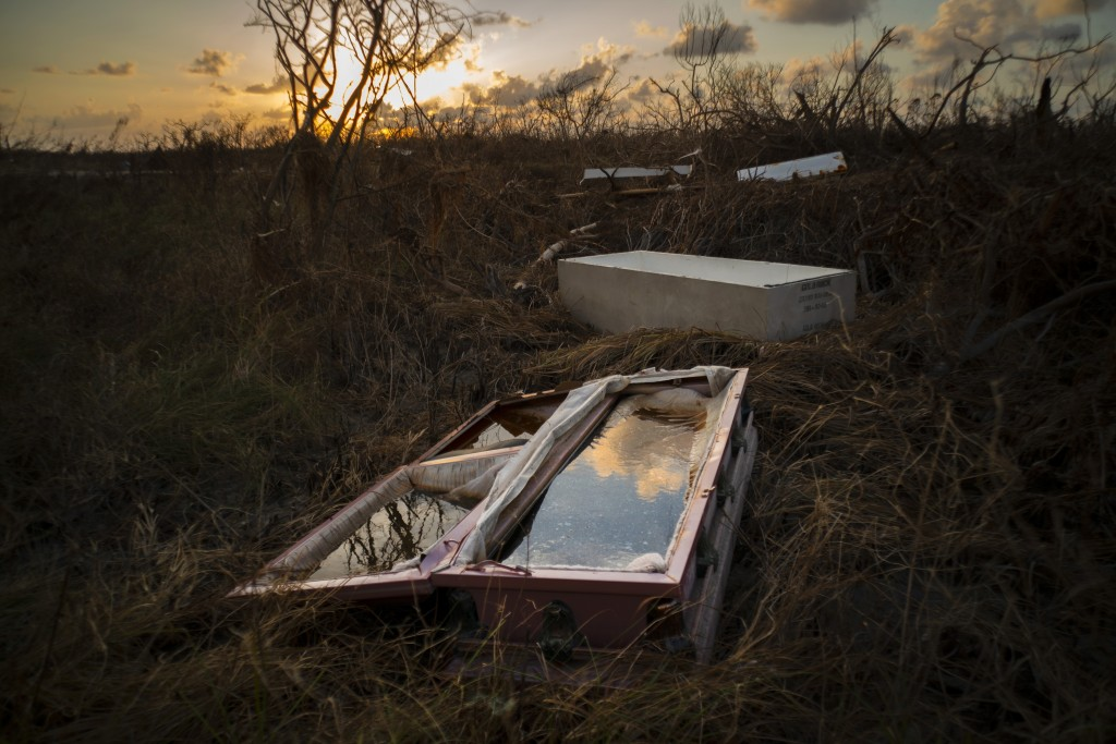 In this Sept. 11, 2019 photo, a shattered and water-filled coffin lays exposed to the elements in the aftermath of Hurricane Dorian, at the cemetery i...