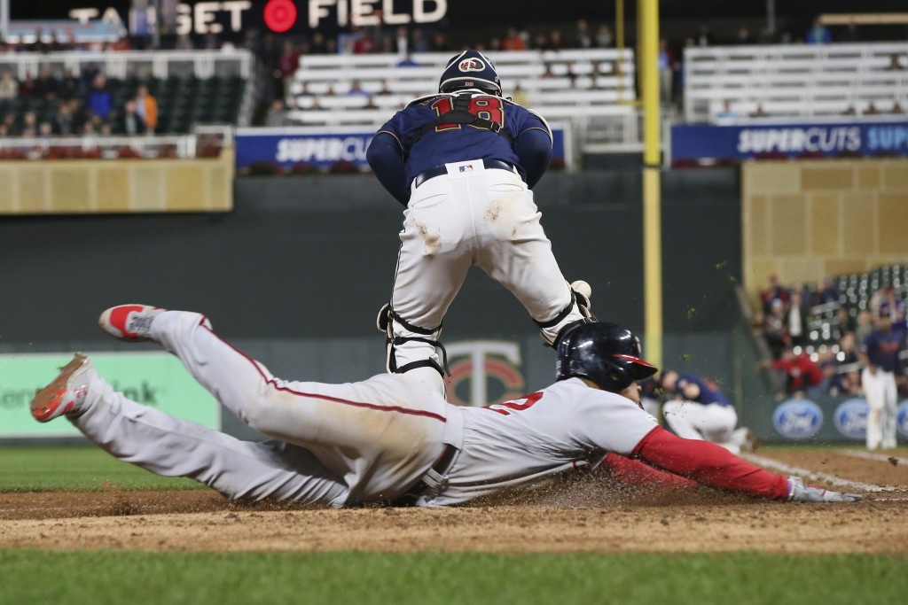 Washington Nationals' left fielder Juan Soto, right, scores on a triple by Asdrubal Cabrera as Minnesota Twins' catcher Mitch Garver chases the ball i