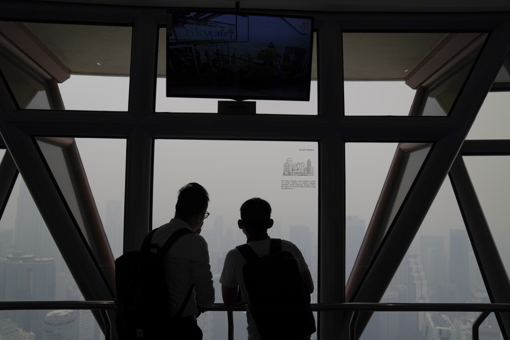 Tourists look out of Kuala Lumpur Tower as city stands shrouded with haze in Kuala Lumpur, Malaysia, Friday, Sept. 13, 2019. Malaysian authorities pla