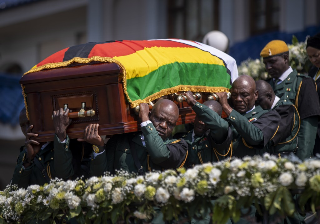 The casket of former president Robert Mugabe is carried by the presidential guard to an air force helicopter for transport to a stadium where it will