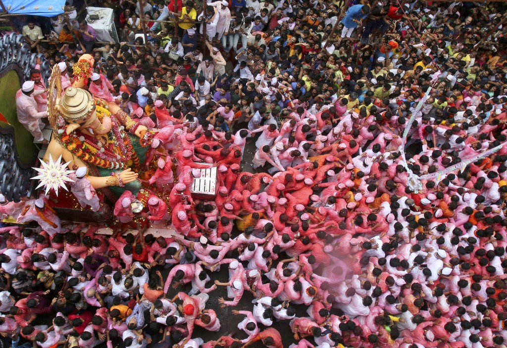 In this Thursday, Sept. 12, 2019, file photo, devotees participate in a procession with a large statue of elephant-headed Hindu god Ganesh in Mumbai, ...