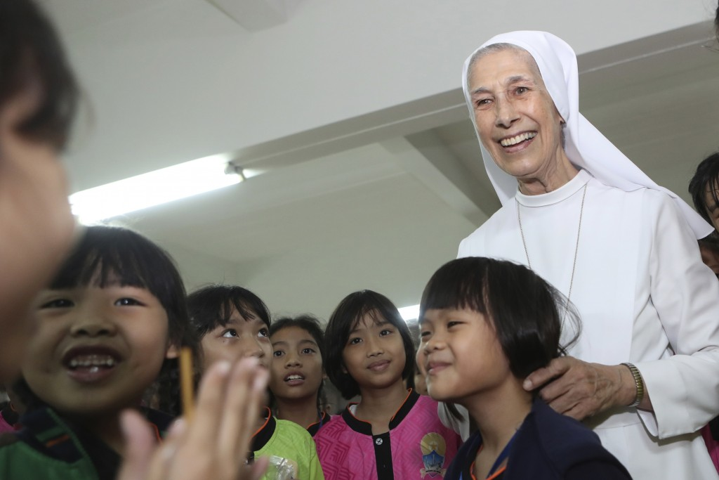 In this  Aug. 27, 2019, photo, ST. Mary's School Vice Principal Sister Ana Rosa Sivori, right, talks to students during a lunch break at the girls' sc