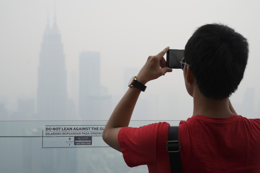 Tourist take a picture from Kuala Lumpur Tower as city stands shrouded with haze in Kuala Lumpur, Malaysia, Friday, Sept. 13, 2019. Malaysian authorit