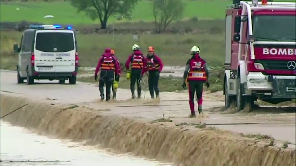 In this image made from video provided by Atlas, firefightters attach ropes to an overturned vehicle in which two people were drowned by floodwater, i...