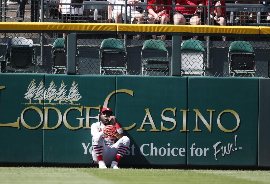St. Louis Cardinals left fielder Marcell Ozuna sits at the base of the left field wall after failing to catch a solo home run off the bat of Colorado