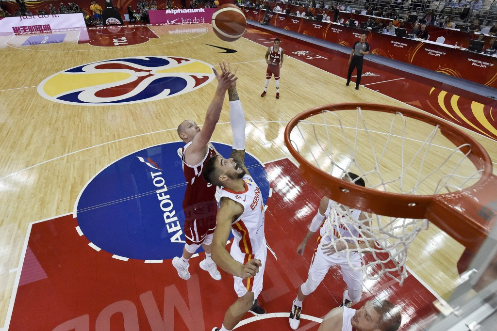 Willy Hernangomez Geuer of the Spain, center, fights for a ball against Poland, rear, during the Basketball World Cup Quarter-Finals between Spain and