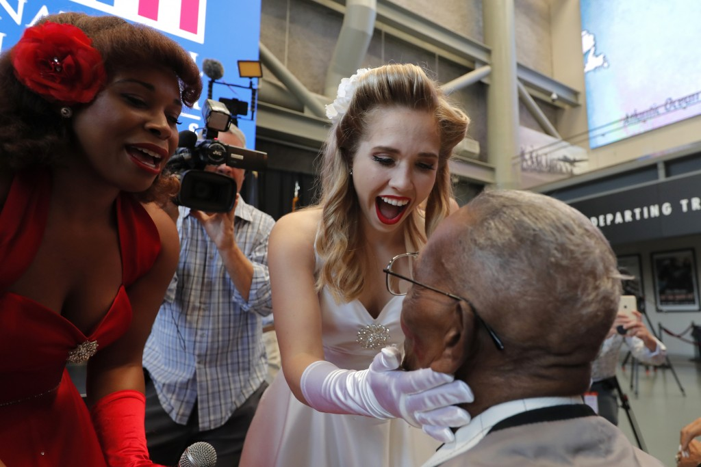 The Victory Belles plant kisses on World War II veteran Lawrence Brooks after singing him happy birthday, celebrating his 110th birthday at the Nation