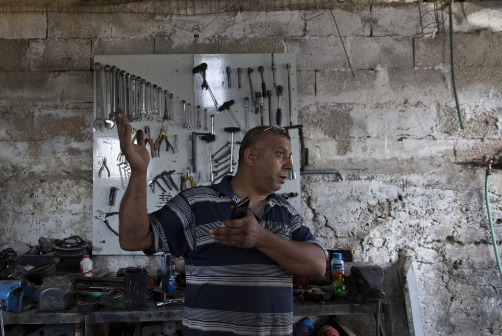 In this Wednesday, Sept. 11, 2019 photo, Palestinian Barhoum Saleh gives an interview at his roadside mechanic shop, near the West Bank Israeli settle...