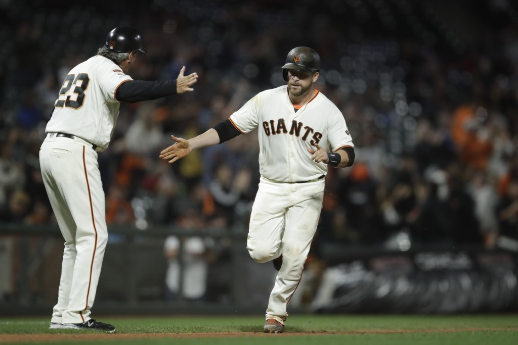 San Francisco Giants' Stephen Vogt, right, celebrates with third base coach Ron Wotus (23) after hitting a two-run home run off Pittsburgh Pirates' Mi...