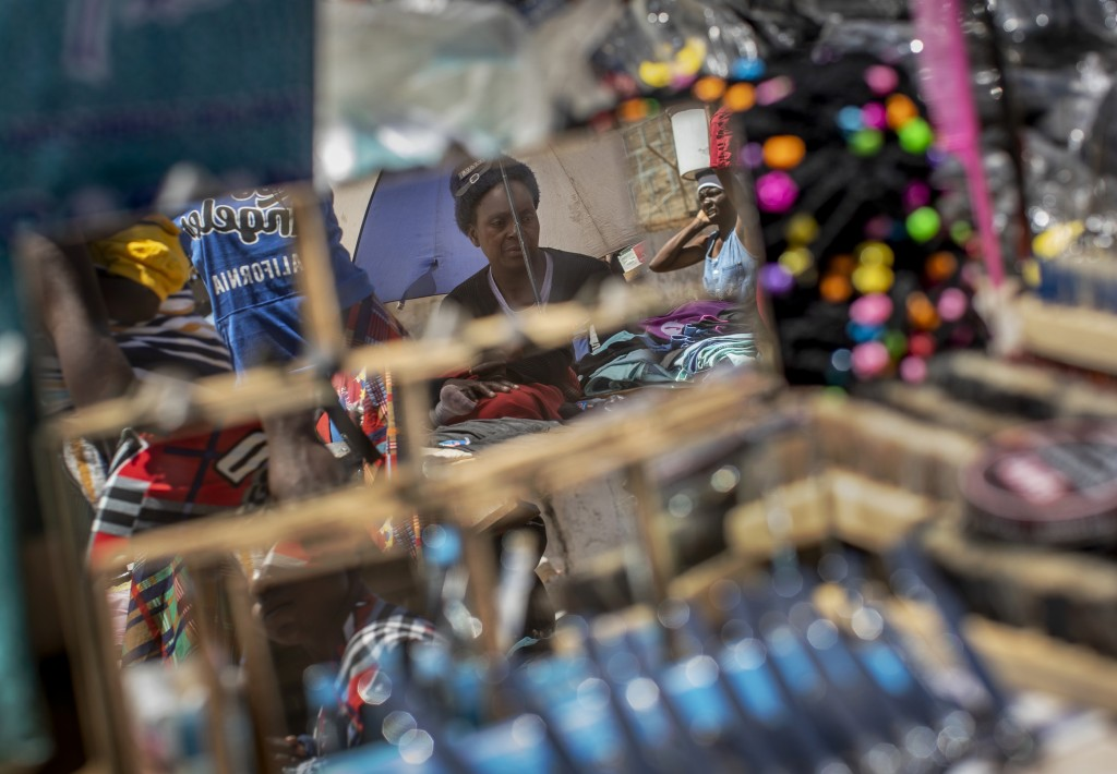 A street seller is seen reflected in mirrors for sale, at a market in the low income neighborhood of Mbare, known to have many supporters of former pr...