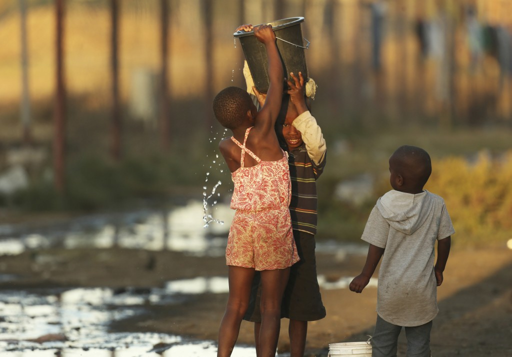 Children help each other to carry a bucket filled with water in Harare, Sept. 8, 2019. Shortages of electricity, water, fuel and cash are the latest s...