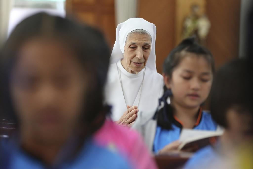 In this Aug. 27, 2019, photo, ST. Mary's School Vice Principal Sister Ana Rosa Sivori, center, and students pray inside a church at the girls' school