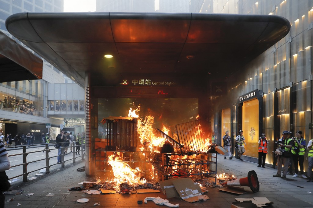 In this Sunday, Sept. 8, 2019, file photo, a fire set by protesters burns at an entrance to the Central MTR subway station in Hong Kong. Thousands of ...
