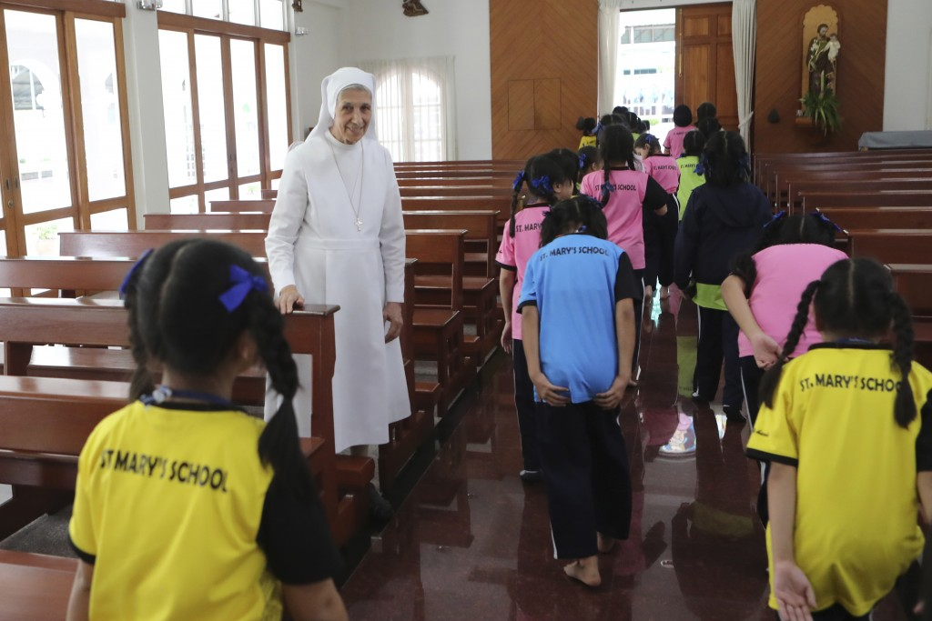 In this Aug. 27, 2019, photo, ST. Mary's School Vice Principal Sister Ana Rosa Sivori, second left, watches as students leave a church at the girls' s