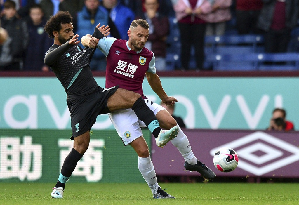 Liverpool's Mohamed Salah, left, and Burnley's Erik Pieters battle for the ball during the English Premier League soccer match at Turf Moor, Burnley, ...