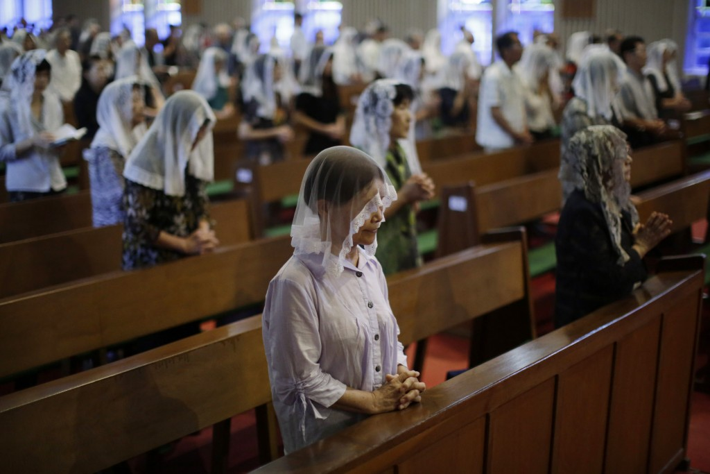 FILE - In this Aug. 9, 2015, file photo, Catholics offer prayers at an early morning Mass to pay respect to the victims of the atomic bombing at the U