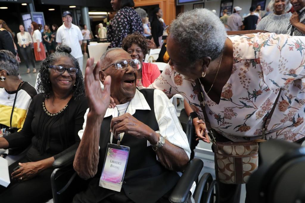 Edith Francisco, a fellow church member, greets World War II veteran Lawrence Brooks as he celebrates his 110th birthday at the National World War II ...
