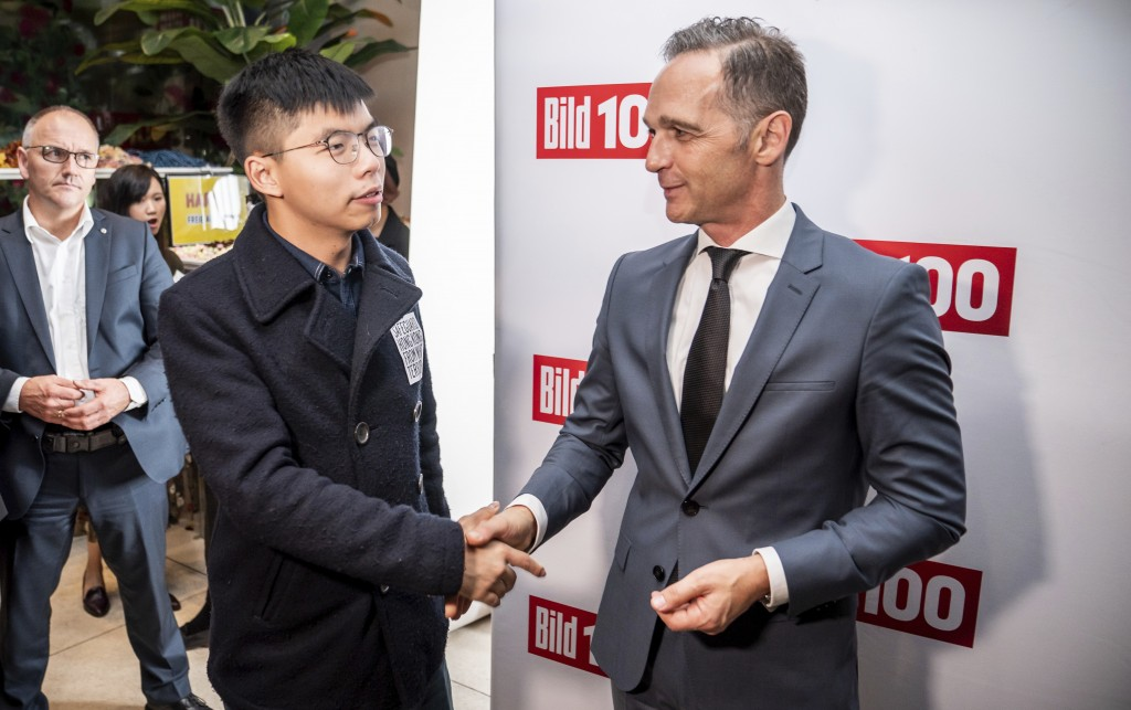 German Foreign Minister Heiko Maas, right, and Hong Kong activist Joshua Wong, left, shake hands during a reception of a German news paper in Berlin, ...