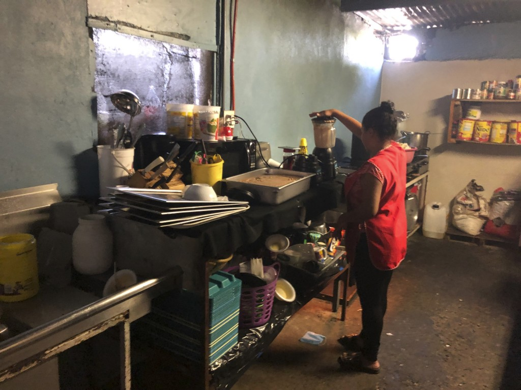 Honduran migrant Dunea Romero, 31, helps helps make Honduran style nachos at the migrant shelter where she is living in Tijuana, Mexico, as she waits