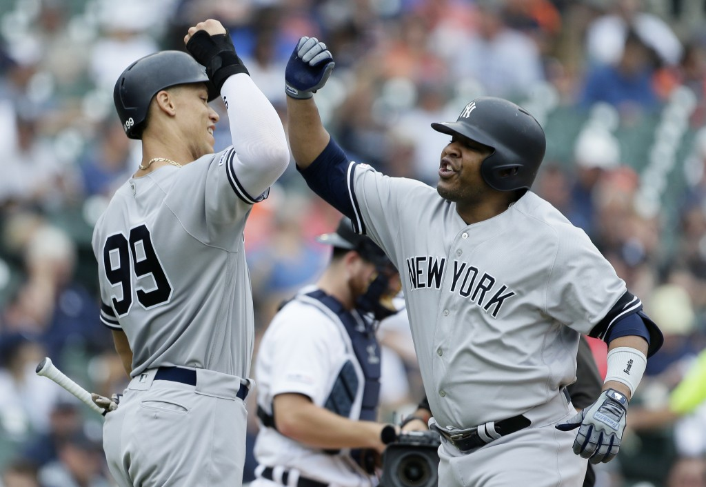 New York Yankees' Edwin Encarnacion, right, celebrates his two-run home run against the Detroit Tigers with Aaron Judge (99) during the third inning o...