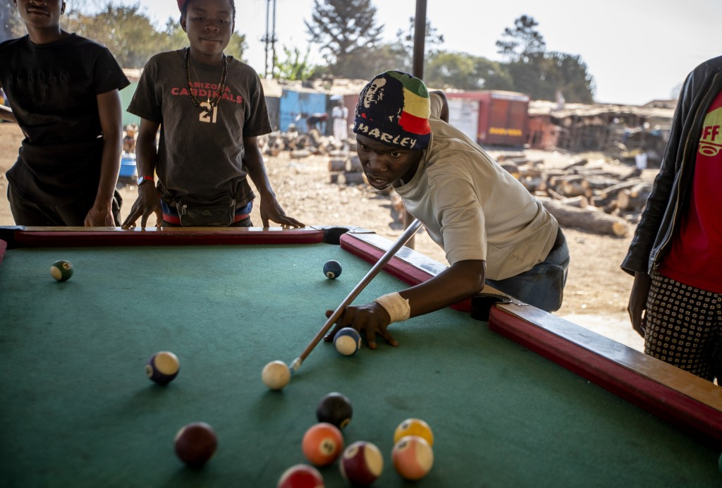 Young men play a game of pool in the open air in Norton, west of the capital Harare, in Zimbabwe, Sept. 10, 2019. Harare once enjoyed a reputation for...