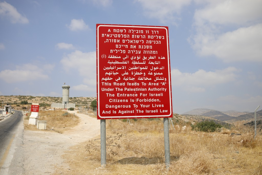 A sign in Hebrew, Arabic and English at an Israeli military roadblock warns against entry to Palestinian-controlled territory, near Bardala in the Isr