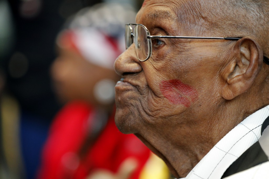 World War II veteran Lawrence Brooks sports a lipstick kiss on his cheek, planted by a member of the singing group Victory Belles, as he celebrates hi...