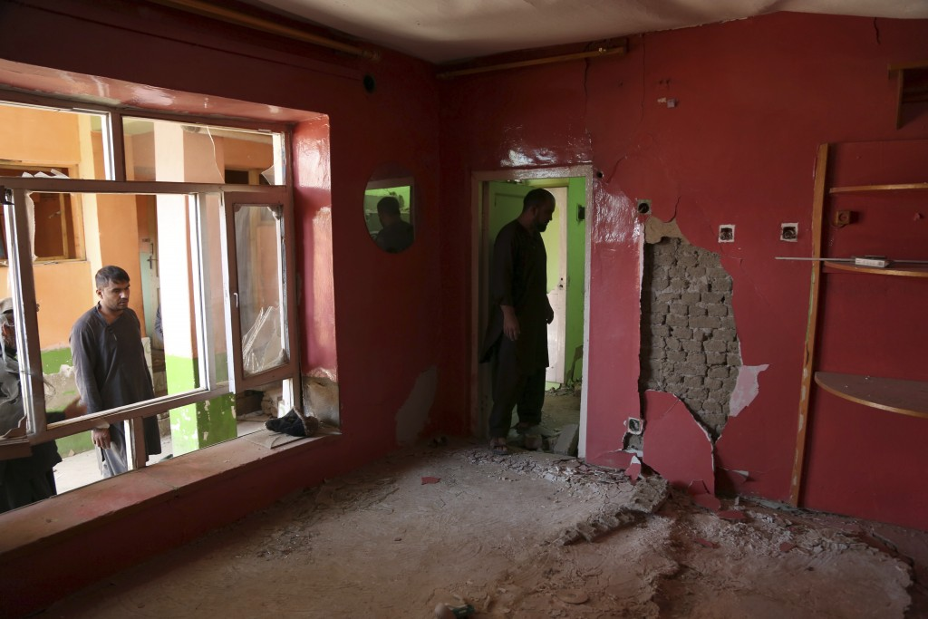 In this Tuesday, Sept. 10, 2019 photo, Afghans inspect their damaged house after a large explosion last week near a compound housing several foreign o...