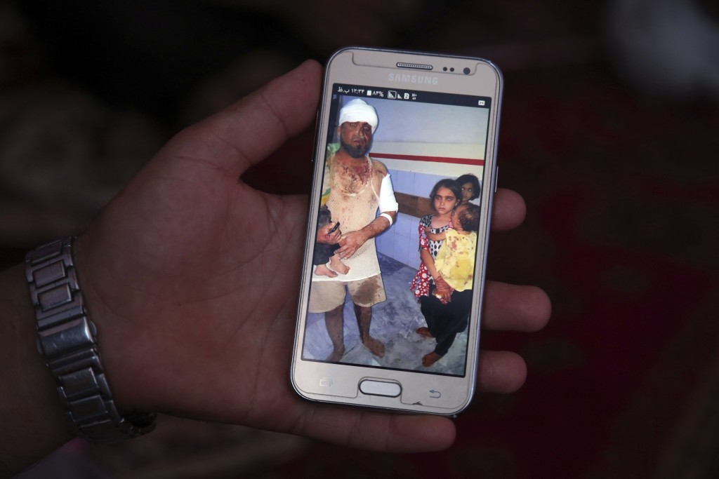In this Tuesday, Sept. 10, 2019, photo, Abdul Latif shows a photograph of Zaki, dusty and bleeding and clutching a child, after a large explosion last...