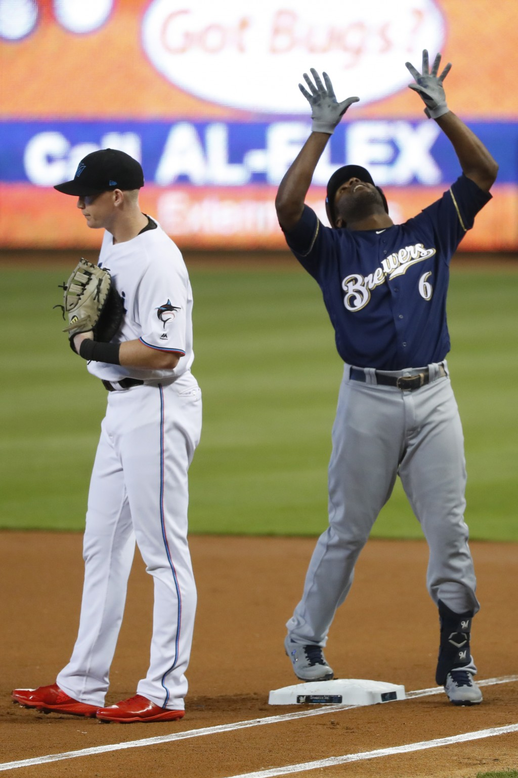 Milwaukee Brewers' Lorenzo Cain (6) celebrates a base hit next to Miami Marlins right fielder Garrett Cooper during the first inning of a baseball gam...