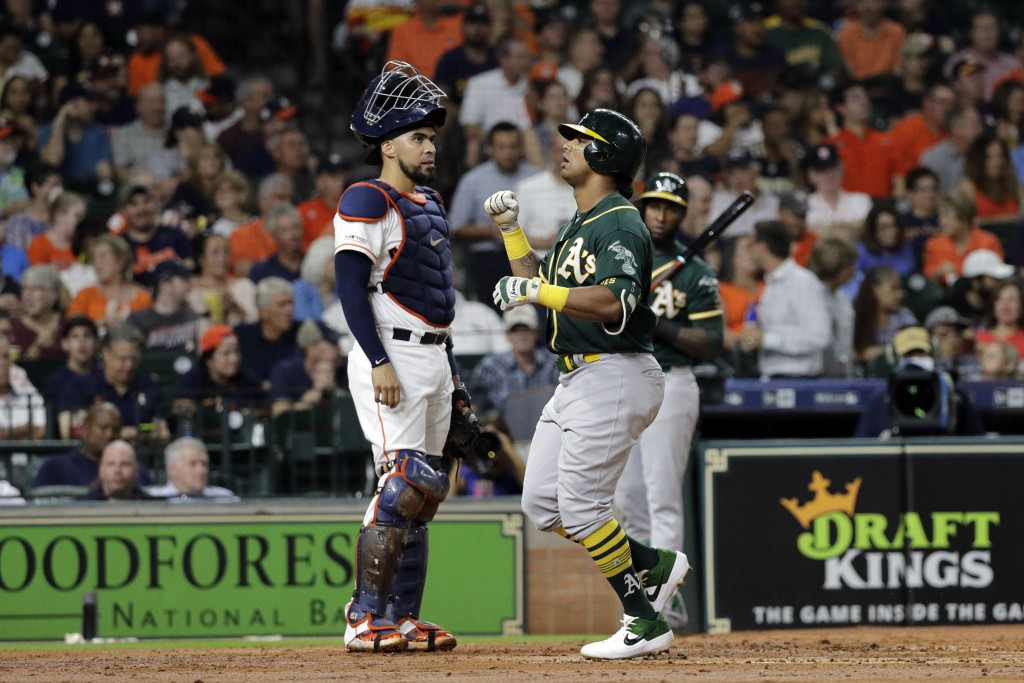Oakland Athletics' Khris Davis, right, celebrates after hitting a two-run home run as Houston Astros catcher Robinson Chirinos stands behind home plat...