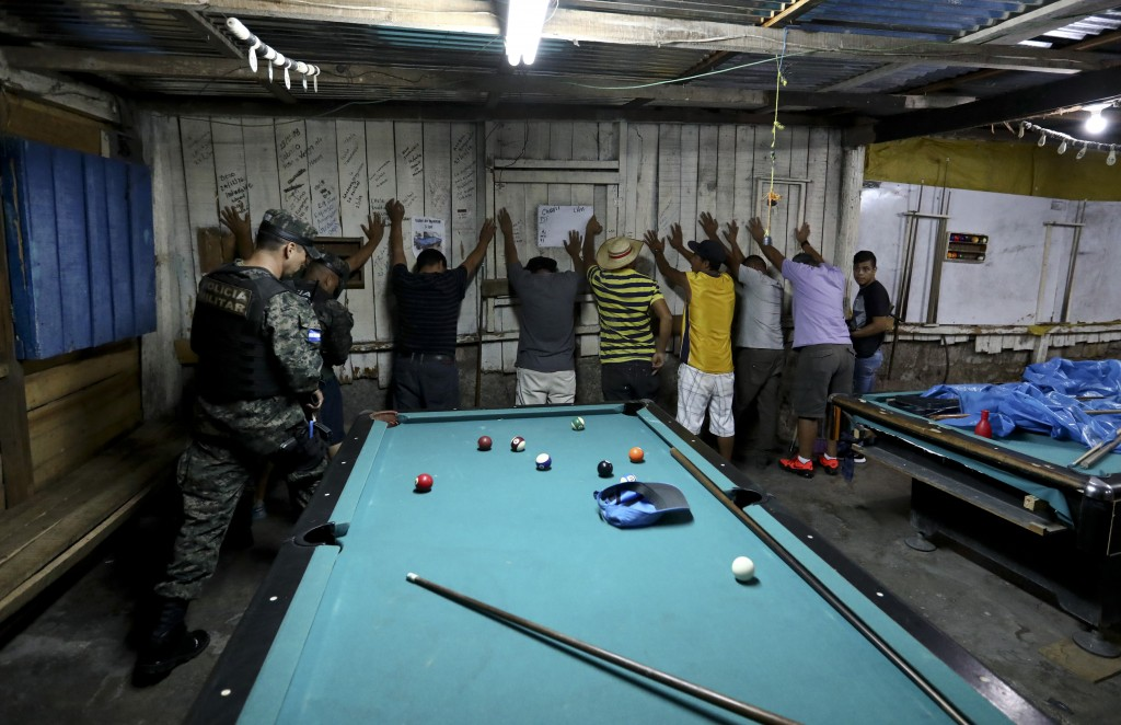 In this Aug. 21, 2019 photo, soldiers enter a pool hall during their routine patrol in Tegucigalpa, Honduras. Ironically, the extradition of drug capo...