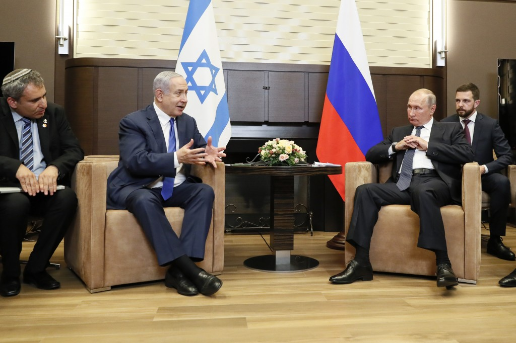 Russian President Vladimir Putin, center right, and Israeli Prime Minister Benjamin Netanyahu talk during their meeting in Sochi, Russia, Thursday, Se...