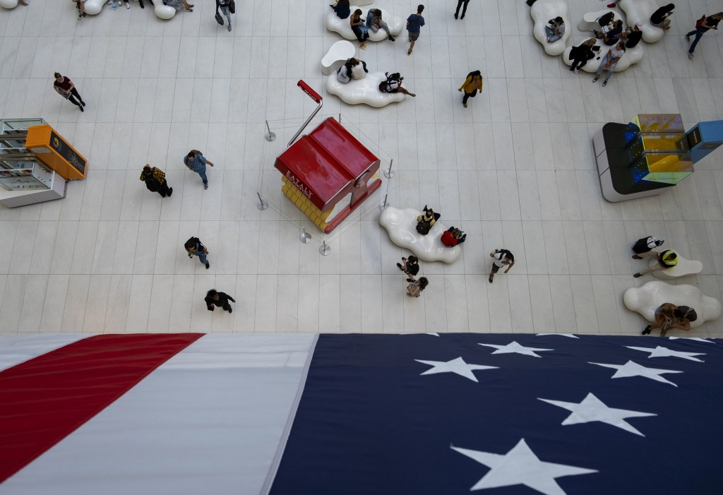 People walk under a flag in the Oculus transportation hub Wednesday, Sept. 11, 2019, in New York. From Europe to Japan, President Donald Trump has sti...