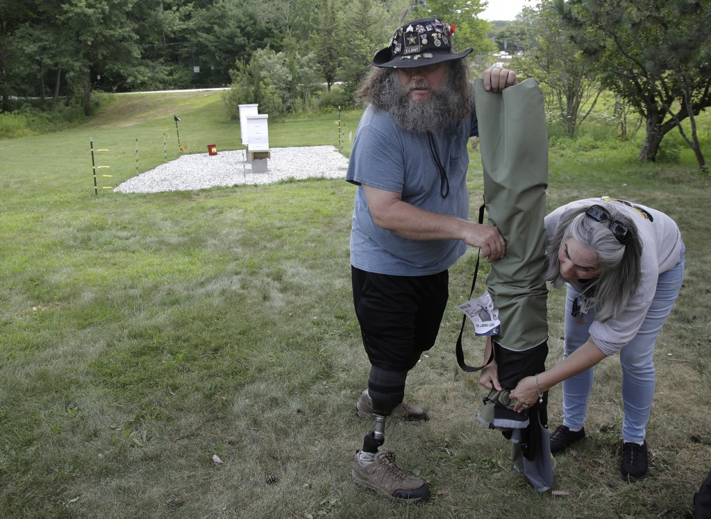 In this Aug. 7, 2019 photo, U.S. Army veterans Oscar Toce, left, and Wendi Zimmermann pack up after beekeeping activities at the Veterans Affairs' bee...