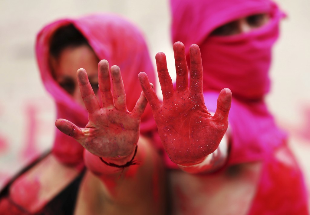 In this Sept. 6, 2019 photo, women with her hands covered in red paint protest against the murders of sex workers, at Mexico City's iconic Angel of In