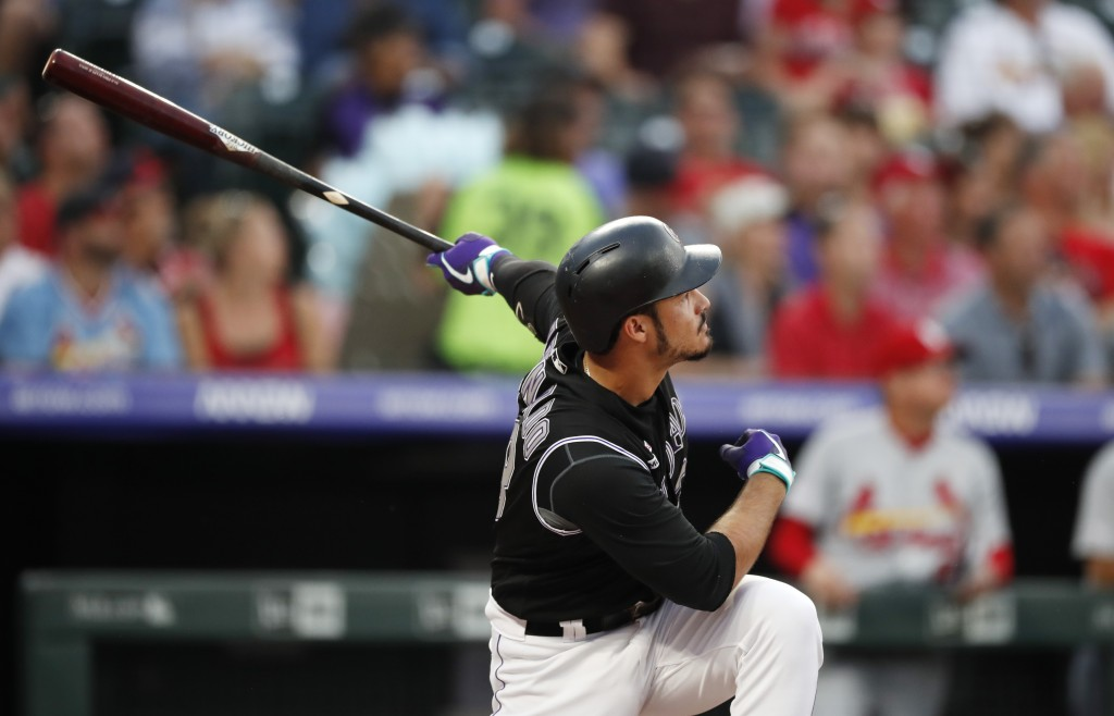 Colorado Rockies' Nolan Arenado watches his two-run home run off St. Louis Cardinals starting pitcher Michael Wacha during the first inning of a baseb