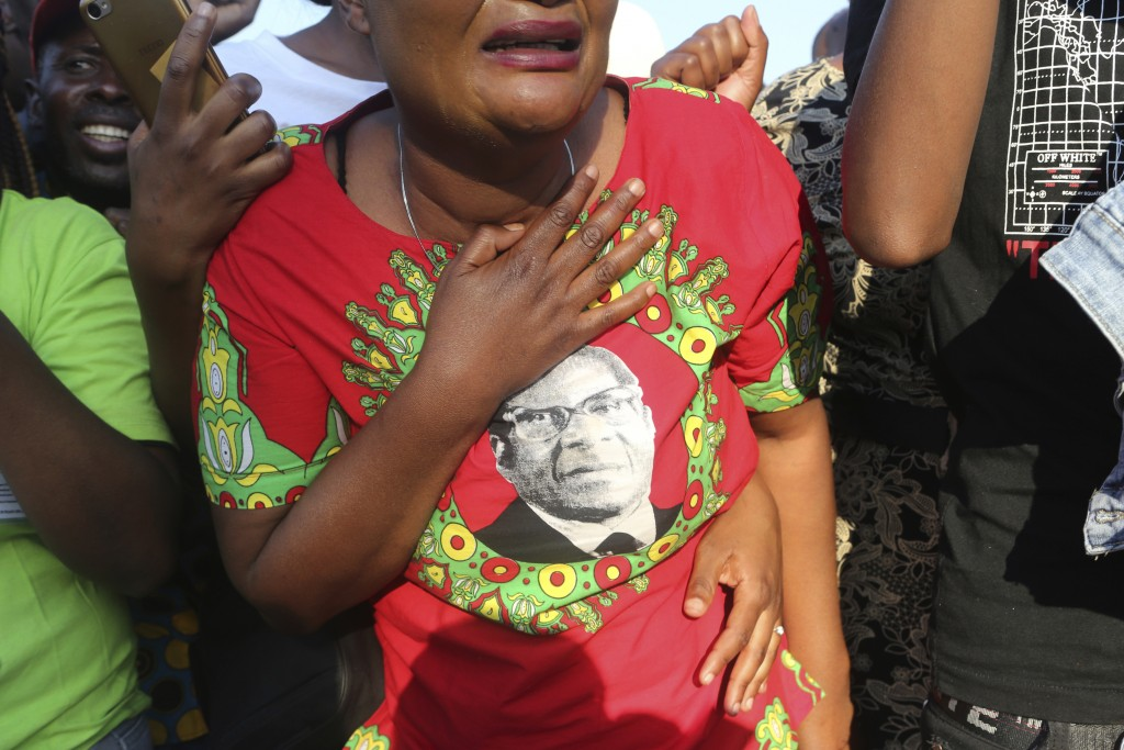 Supporters of Zimbabwe's former ruler Robert Mugabe react upon the arrival of his remains at RG Mugabe airport in Harare, Sept, 11, 2019. As controver...