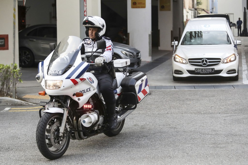 A police motorcycle escorts a hearse, right, carrying the body of former Zimbabwe President Robert Mugabe leaving the Singapore Casket Funeral Parlour