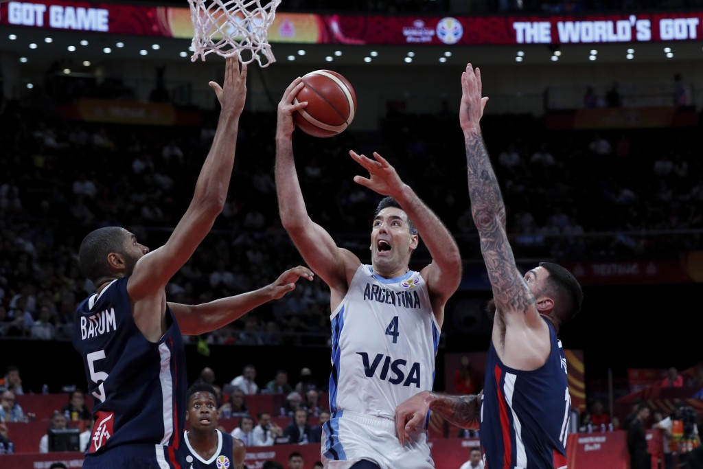 Luis Scola of Argentina goes for a shot over Nicholas Batum, left, and Vincent Poirier of France during their semifinals match for the FIBA Basketball...
