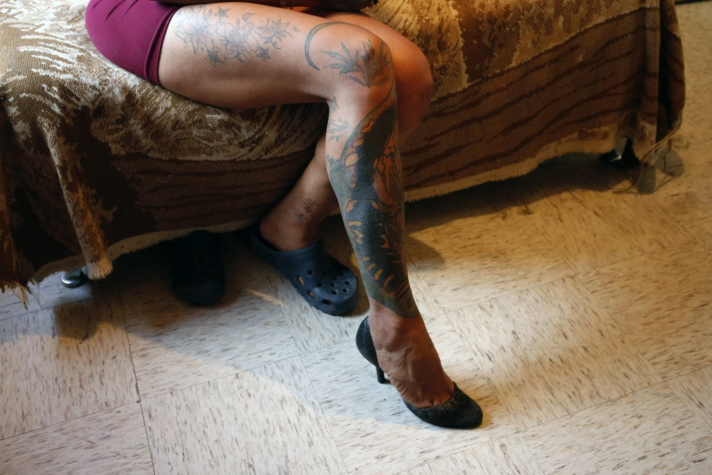 In this Aug. 17, 2019 photo, trans rights activist Kenya Cuevas sits on the edge of her bed to show off the tattoos on her right leg, in her bedroom i...