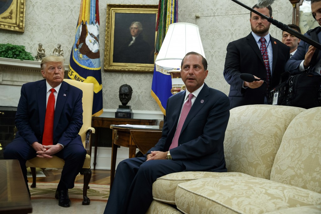 President Donald Trump listens as Secretary of Health and Human Services Alex Azar talks about a plan to ban most flavored e-cigarettes, in the Oval O...