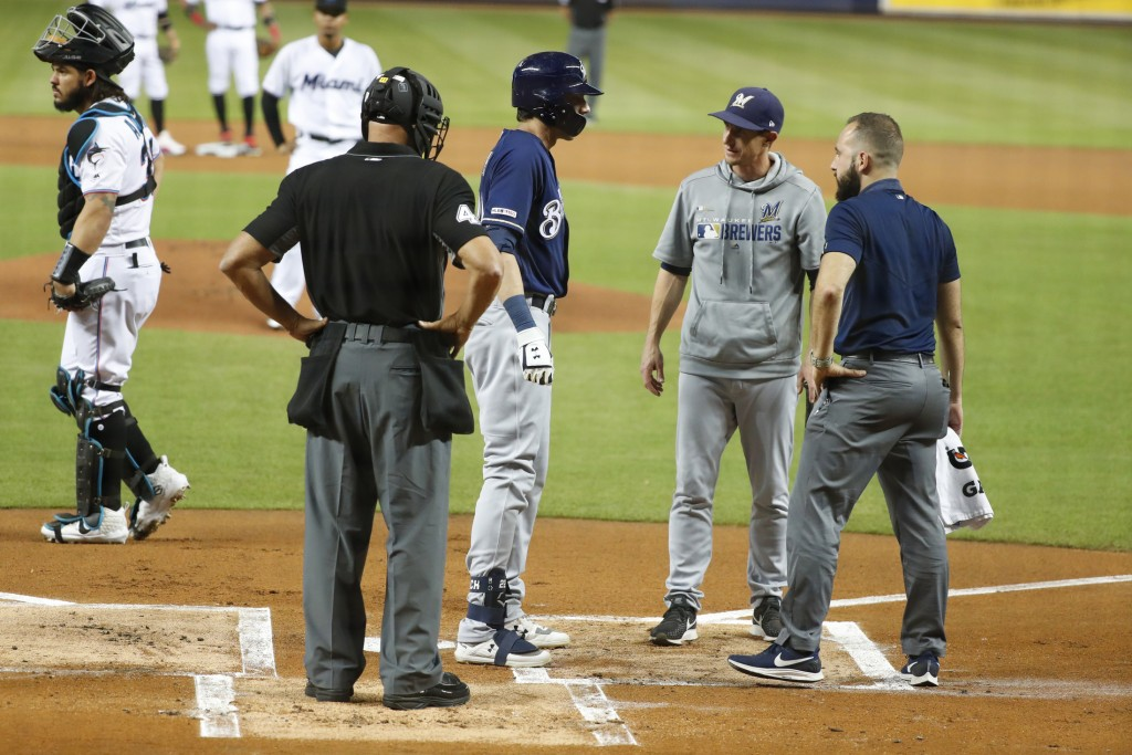 Milwaukee Brewers' Christian Yelich, second from left, is checked on by home plate umpire Kerwin Danley, manager Craig Counsell, second from right, an...