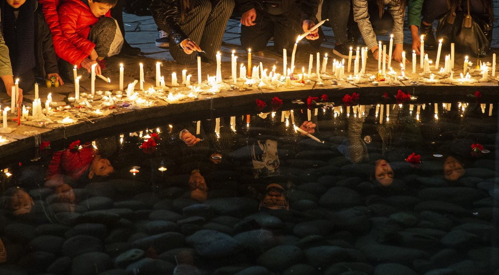 In this Sept. 11, 2019 photo, people light candles at the National Stadium during a vigil marking the anniversary of the 1973 military coup that ouste