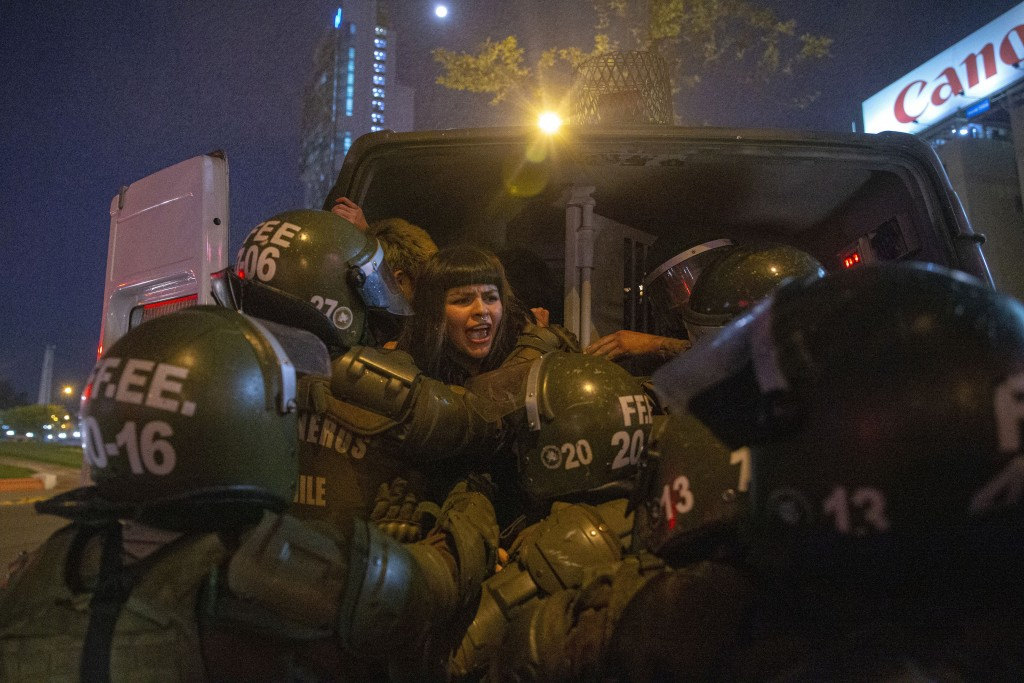 In this Sept. 11, 2019 photo, a woman is detained by police during a feminist protest marking the 46th anniversary of the military coup that ousted th...
