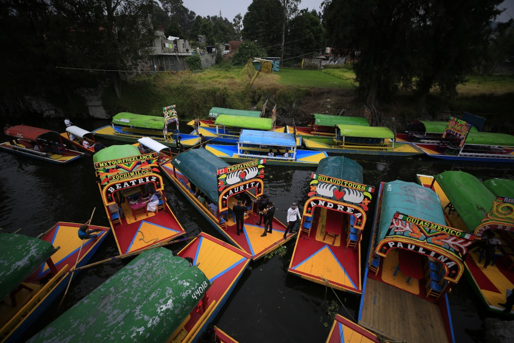 "In this Sept. 6, 2019, photo, boats carrying passengers come in to dock amidst parked ""trajineras,"" the colorful passenger boats typically rented by t"