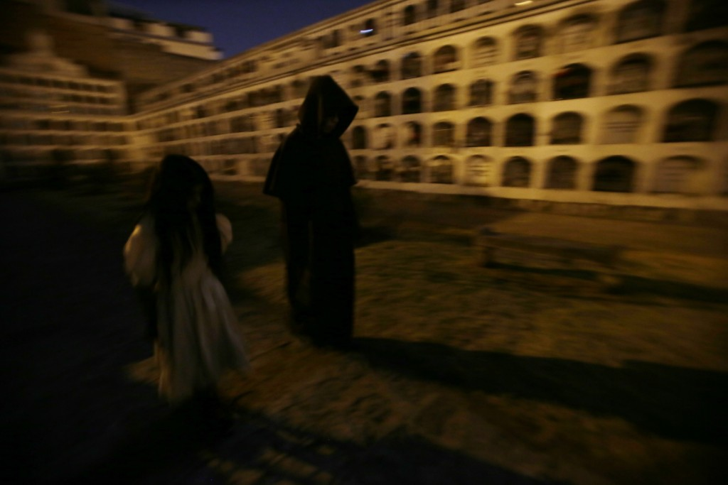 Guides walk under the moonlight at El Tejar cemetery, in downtown Quito, Ecuador, Wednesday, Sept. 11, 2019. The guides in black hooded capes lead tou