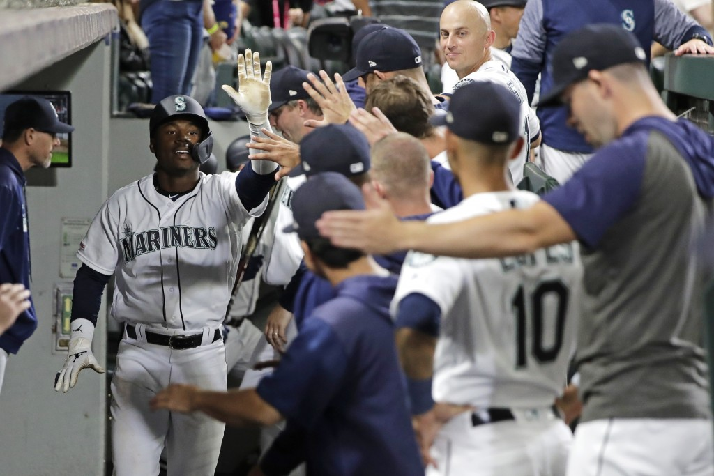 Teammates line up to greet Seattle Mariners' Kyle Lewis, left, in the dugout after he hit a solo home run against the Cincinnati Reds during the fifth...