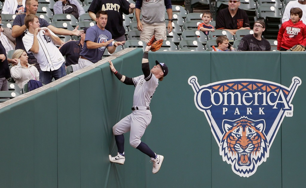 New York Yankees left fielder Clint Frazier climbs up the left field corner to catch a foul fly ball hit by Detroit Tigers' Jake Rogers during the eig...