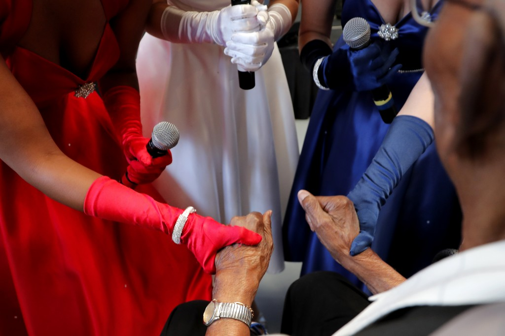 The Victory Belles hold the hands of World War II veteran Lawrence Brooks as they sing him happy birthday celebrating his 110th birthday at the Nation